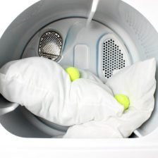 Two pillows in the dryer with two tennis balls