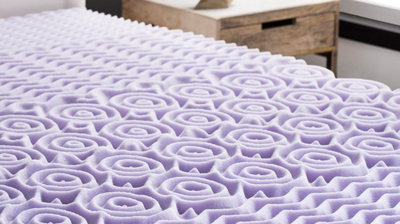 A convoluted pattern topper on top of a queen bed and mattress
