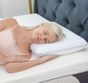 A woman sleeping on her size on a coolin pillow