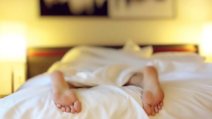 A woman sleeping on her stomach on cotton sheets
