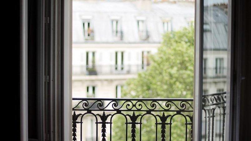 An apartment bedroom with balcony door open
