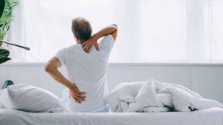 Man sitting on edge of bed with lower back pain and should neck pain