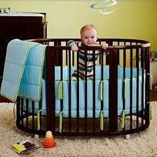 A happy playful baby playing in a padded round crib