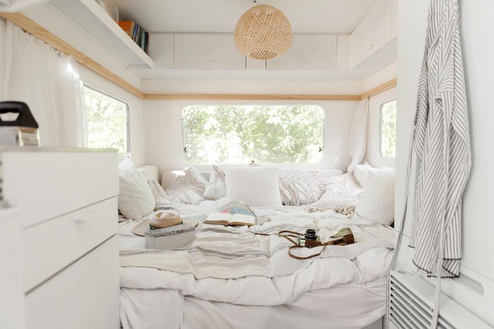 A white RV camper van interior with white bedding, pillows, blanket, bed, mattress