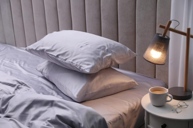 A bed with beautiful light grey pillows in silk bedding and pillowcases and a grey headboard with side lamp and a cup of coffee