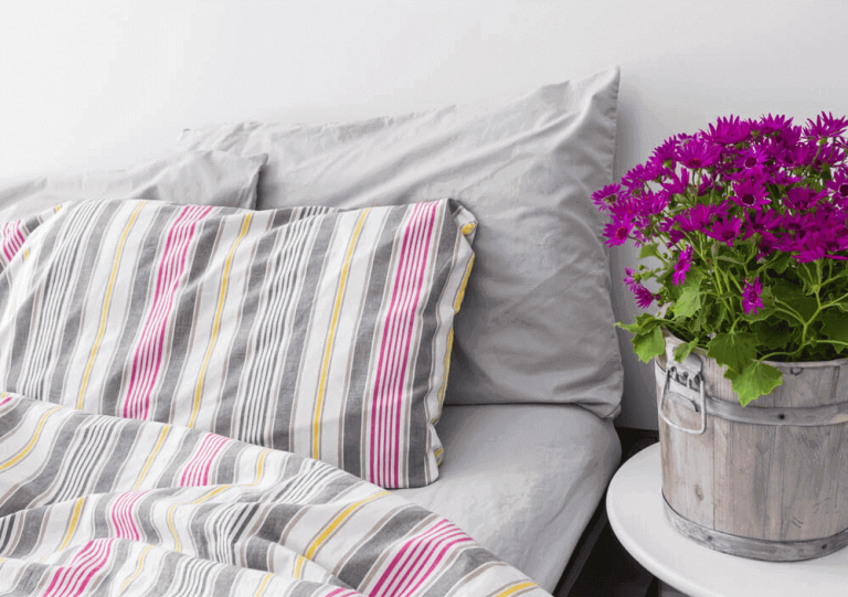 Best linen bedding sets reviews - beautiful bedroom with colored linen and bright flowers.