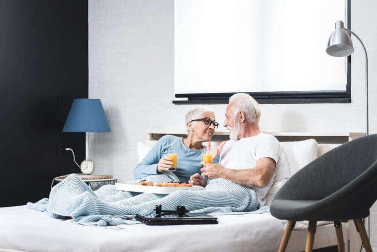 Joyful senior couple having healthy breakfast in bed in their bedroom