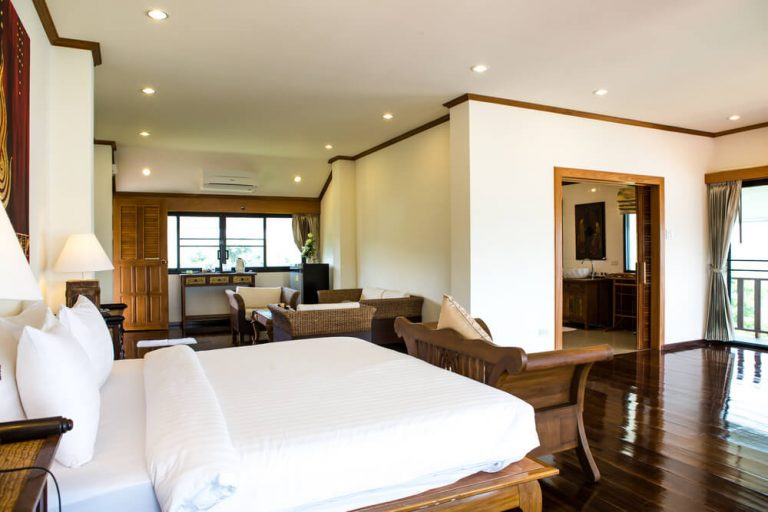 Interior of modern comfortable hotel room with a solid white hotel bed sheets and bedding wooden floors and light.