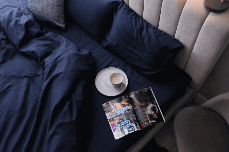 Stylish bed, silky navy bed sheets and linen, coffee, magazine and grey headboard