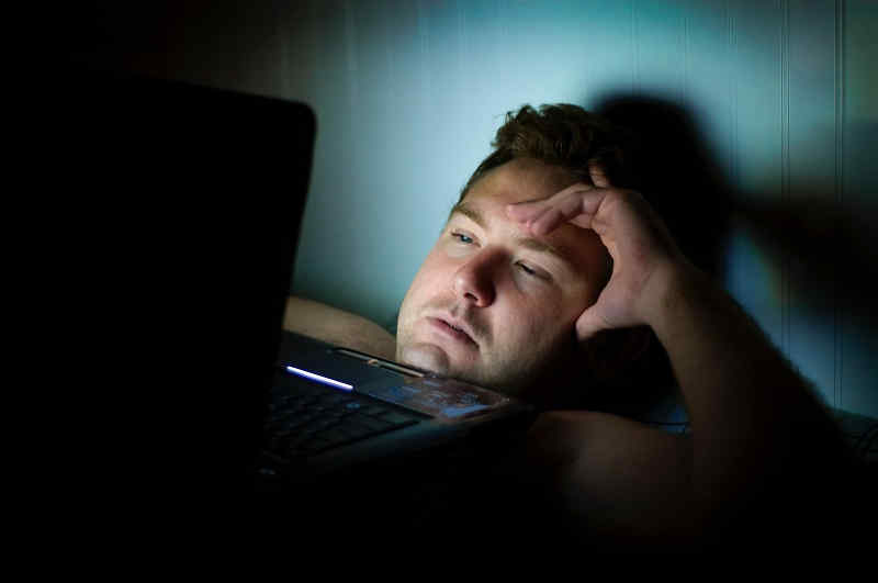 Middle aged man sitting in front of laptop in bed at night time