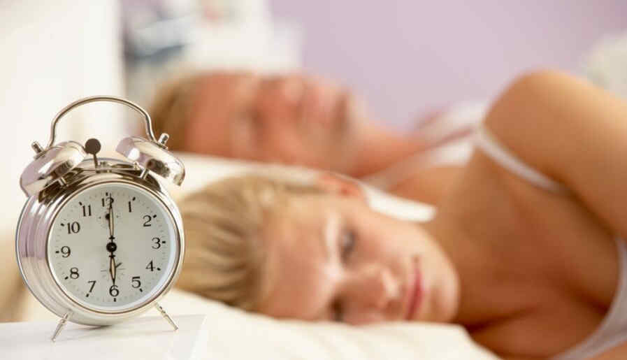 Couple sleeping in bed with alarm clock how much sleep