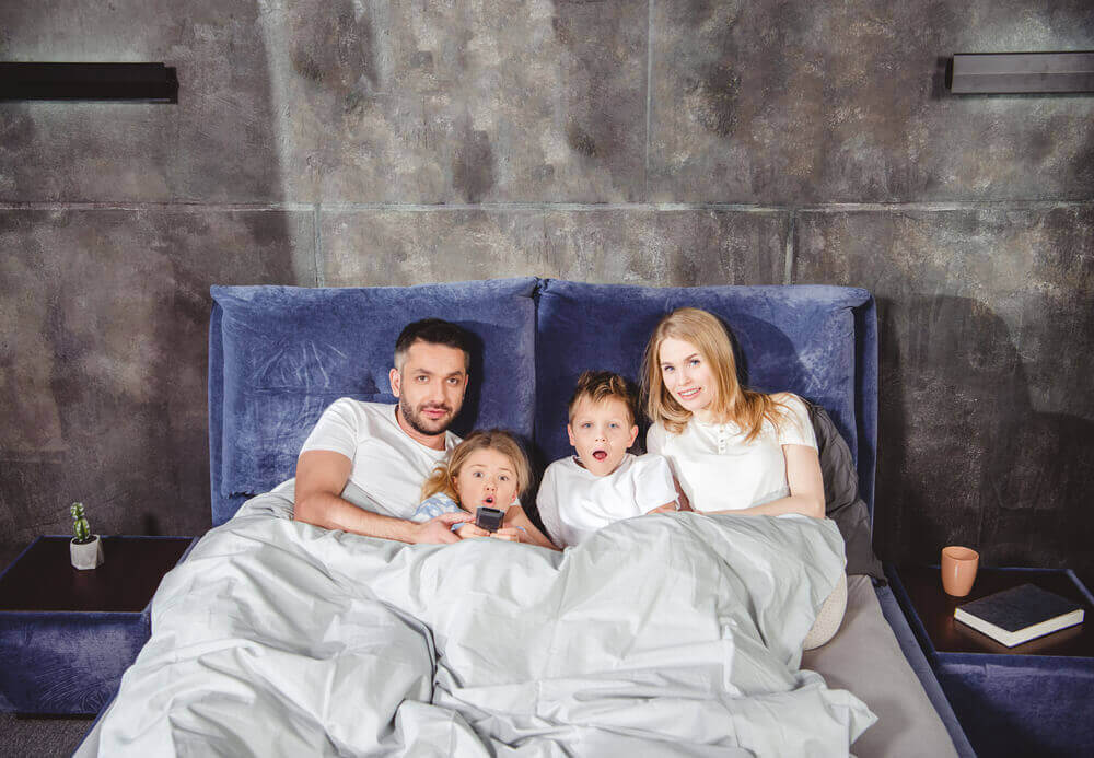 Family watching tv in bed