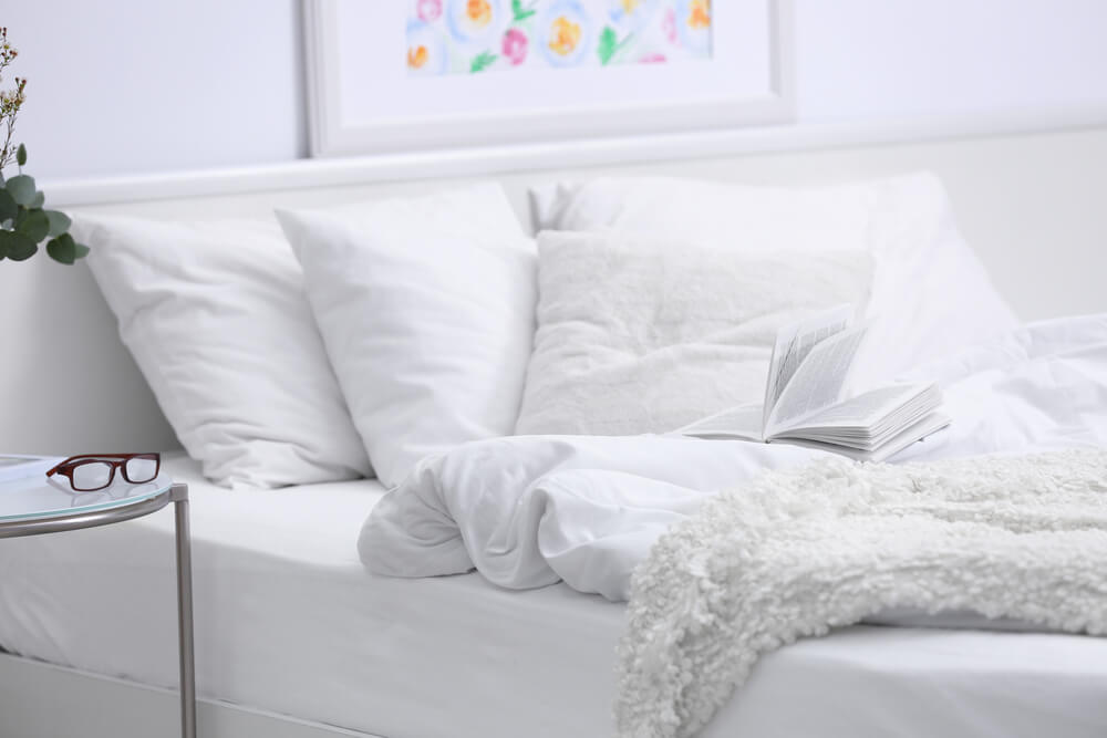 A well made bed with white fitted sheets, white pillow cases and white duvet and blanket