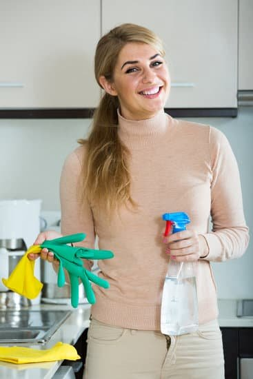 Woman holding cleaning items ready for laundering sheets