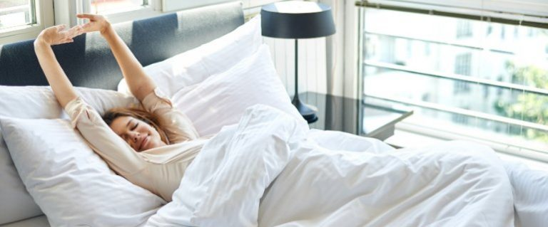 Woman waking up in the morning in fresh clean white bedding