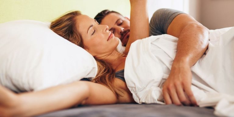 Couple waking up in bed stretching out