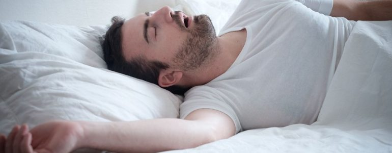 Man lying on his bed snoring while sleeping