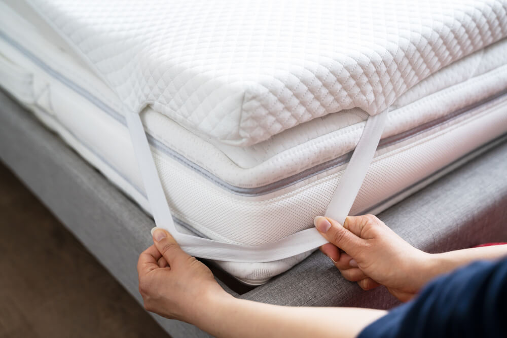 Placing a mattress topper around a mattress