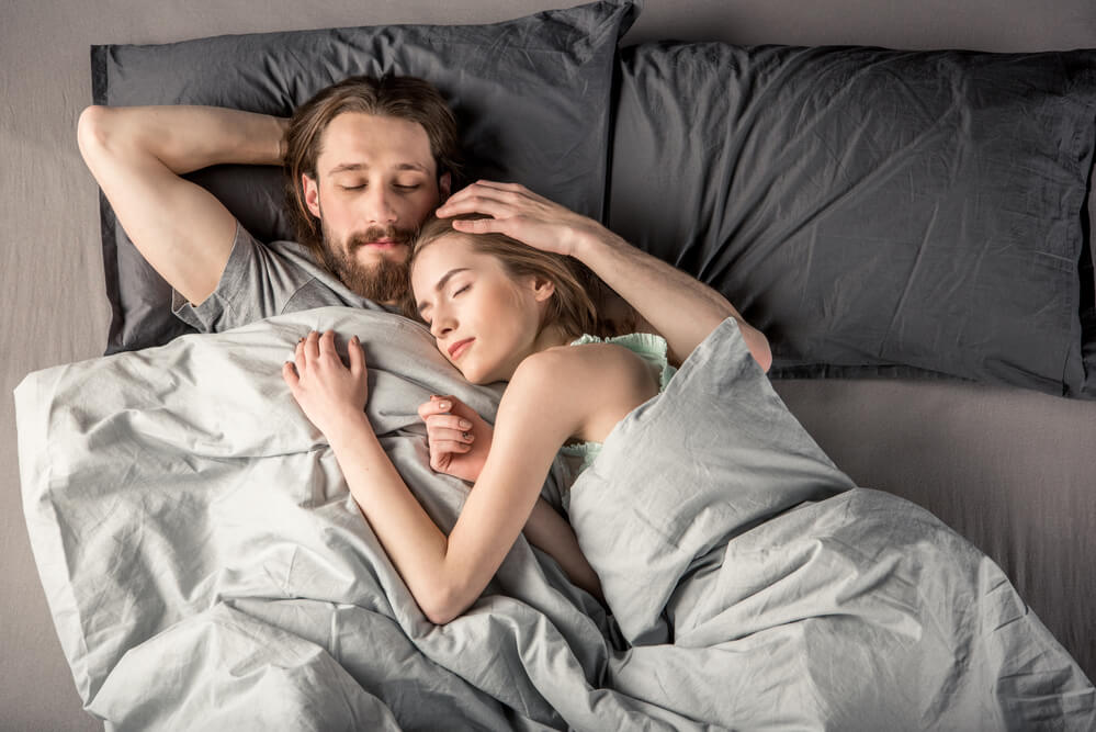 Couple sleeping cool in bed