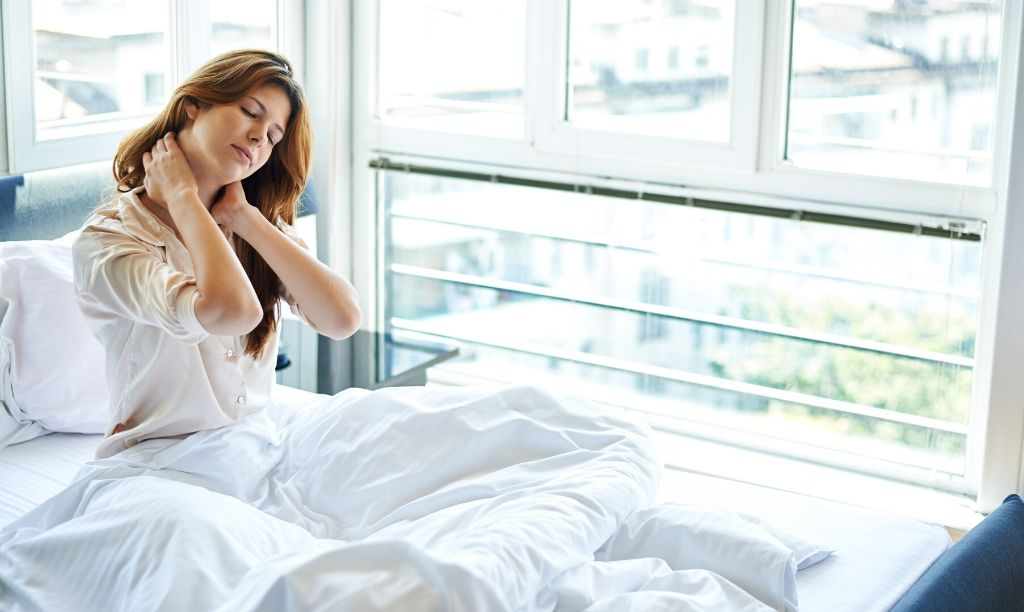Woman waking up in pains and aches