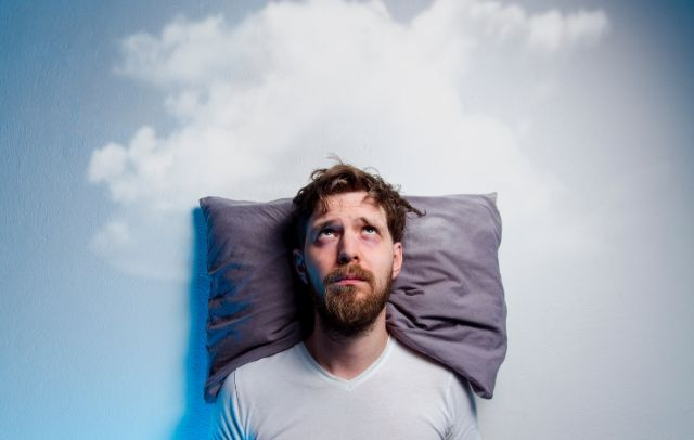 Man resting on pillow having problems sleeping