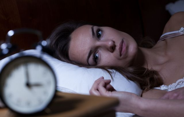 Woman lying in bed looking at clock suffering from insomnia