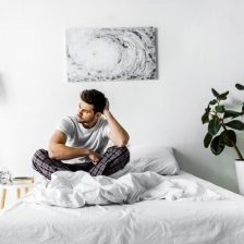 A young man sitting in bed in a white themed bedroom with green plants and beautiful artwall and simple clothes rail.