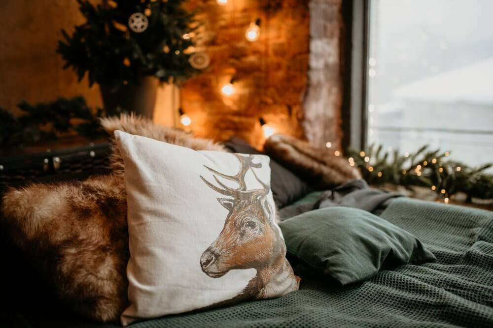 stag print cushion on a bed inspired by nature and animals