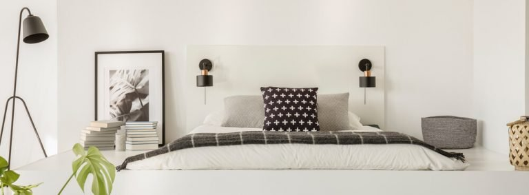 Black lamp standing by the platform with bed with pillows, white sheets, books, posters and woven basket.