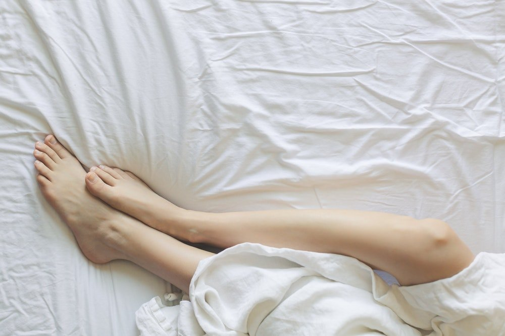 Woman in bed asleep keeping feet outside the covers to cool off
