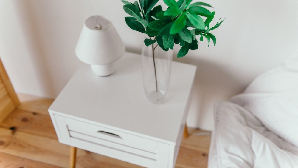 A single white bedside table near a bed