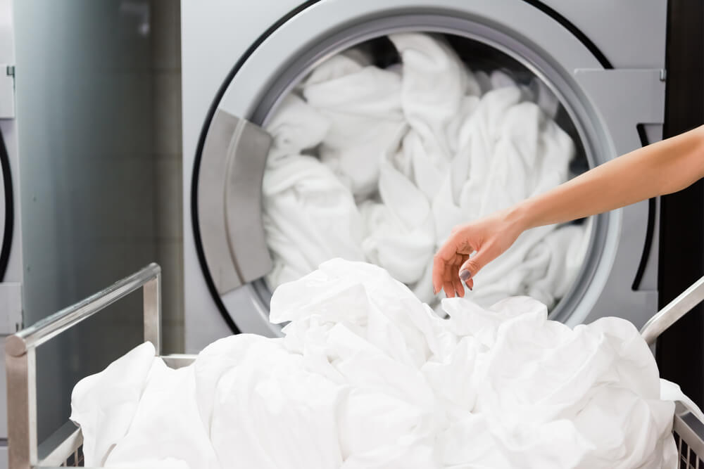 Laundry: White sheets being taken out of the washing machine