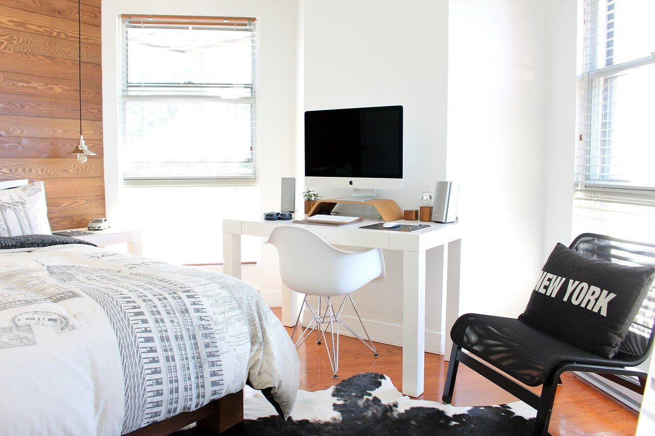 A white bedroom with office space, two windows and a double queen size bed