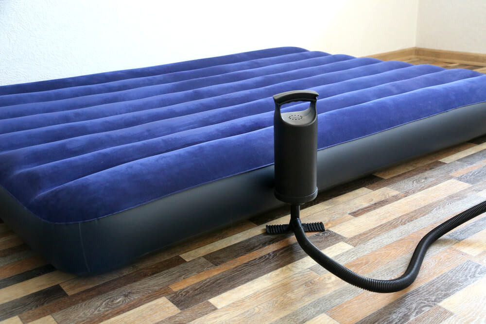 Air bed inflatable mattress and foot pumper on the floor in a bedroom.