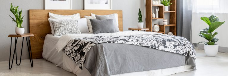 A king bed in gray bedding, pillow arragement, wooden headboard side table bedroom decor