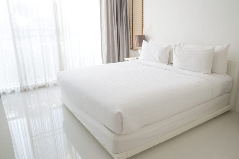 A white bed in a white bedroom with a white bed frame