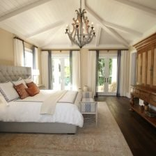 A large master bedroom with king bed and nightstands, rug under bed, large ceilings and large bay windows