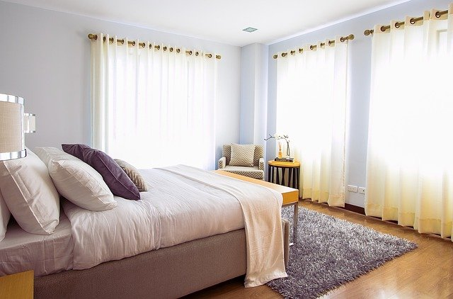 A standard bedroom with a queen bed and nightstands, shaggy gray rug under bed, and large bay windows