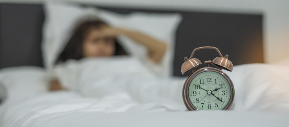 Woman awake at night looking at the clock