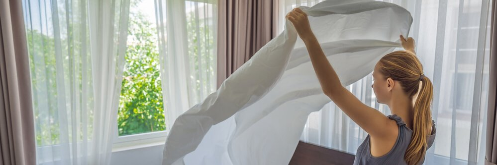 A young woman changing bedding and fitting in a fitted sheet.