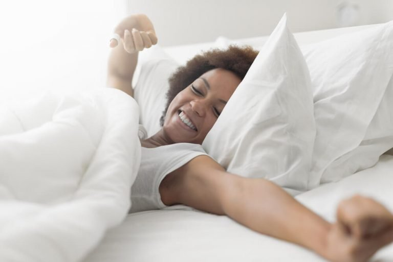 A woman waking up refreshed in clean white percale bedding.