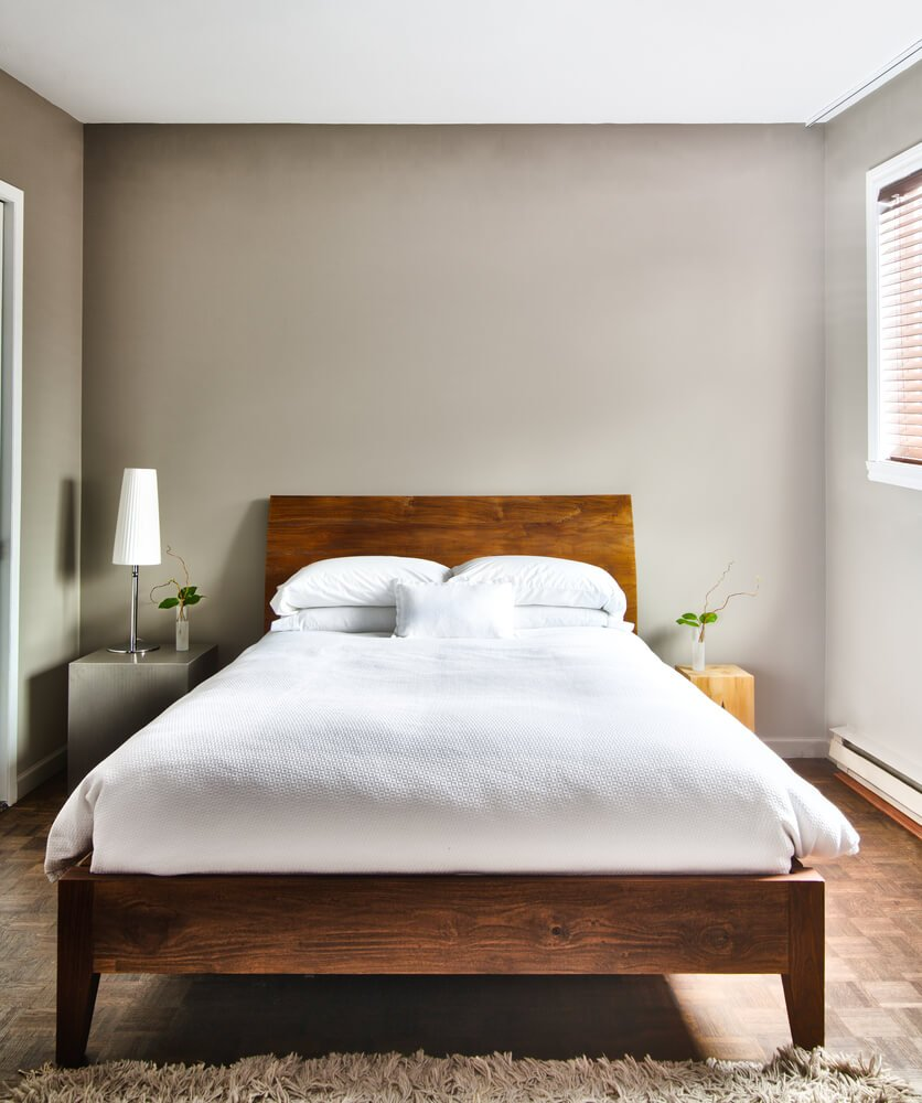 A clean and minimalist bedroom with neutral tones - grey walls, mismatched night stands and white bed linen.