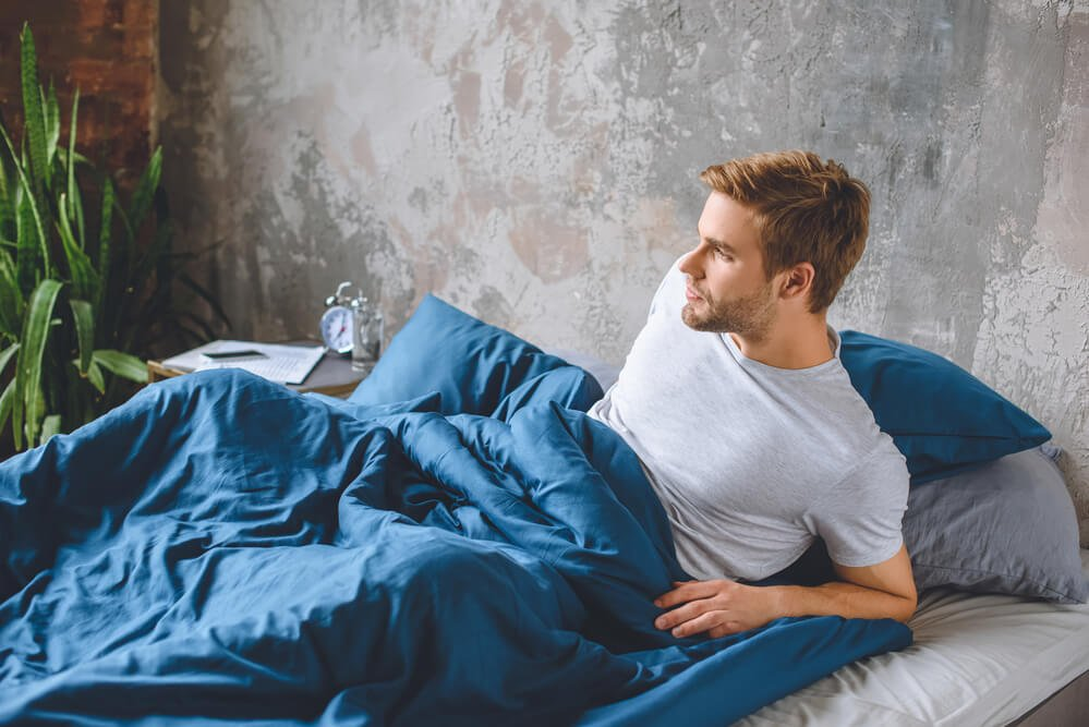 Male waking up in the morning from sleeping in a blue cotton bedding set