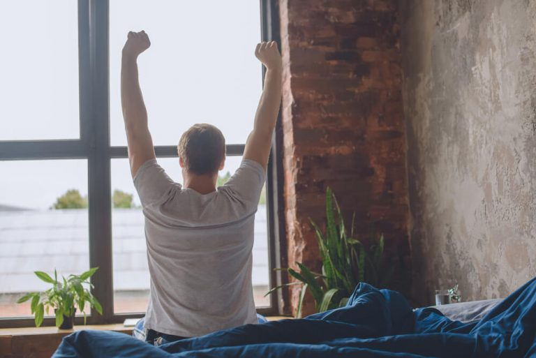 Male stretching in bed waking up