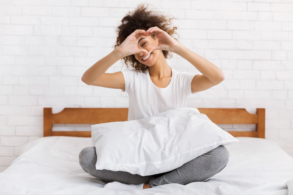 Woman waking up refreshed, well rested and no bed head.