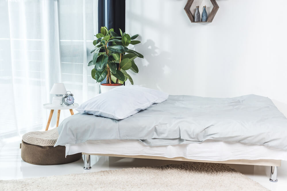 A bright and minimalist bedroom with a bed and light blue and white cotton percale bedding, green plant, white lamp and alarm clock.