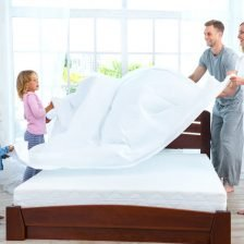 A family of four helping making a bed and changing bed sheets on an encased mattress.