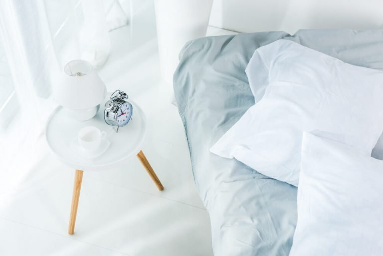 A bed made using celliant powered white and baby blue bed sheets in a bright and white modern bedroom with an alarm clock and small lamp.