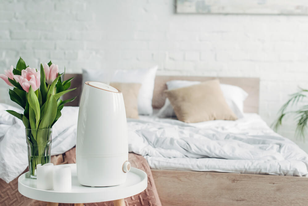 An air humidifier in a near a bed in a bedroom that's bright and airy.