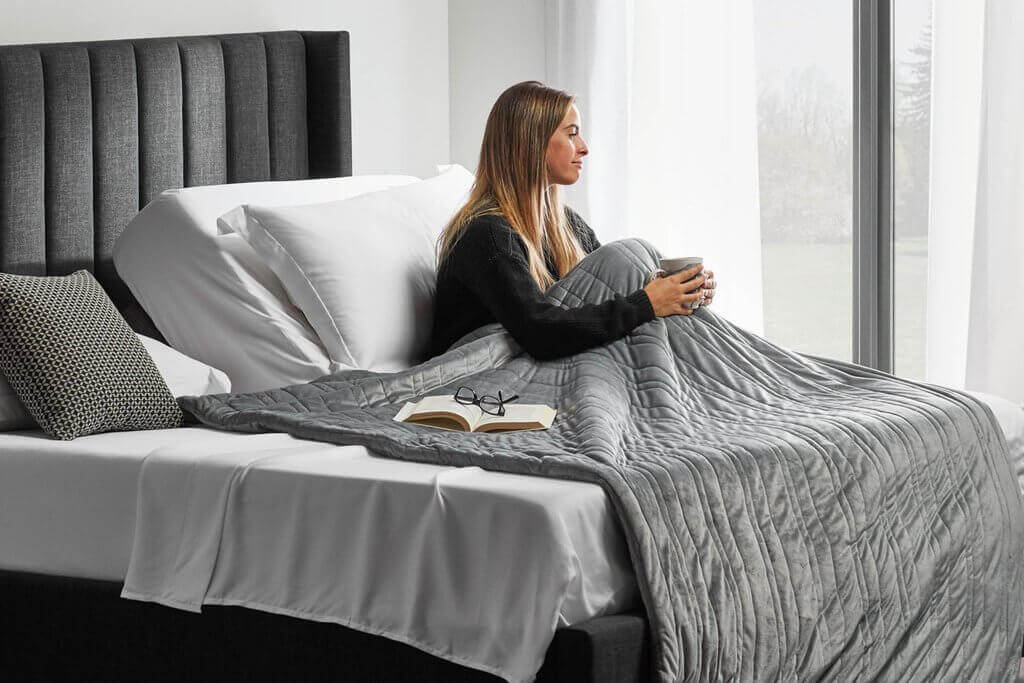 A woman using an weighted blanket on bed for sleep purposes